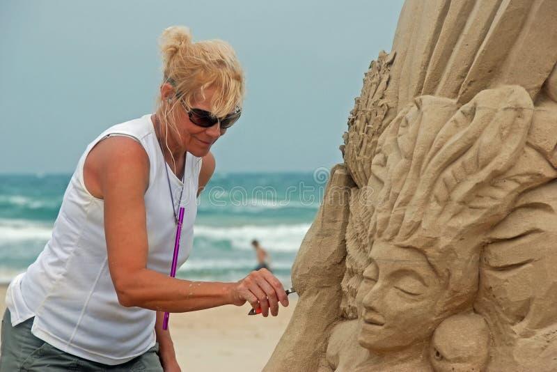 Versanden Sie den Bildhauer, der an Strand arbeitet stockbild