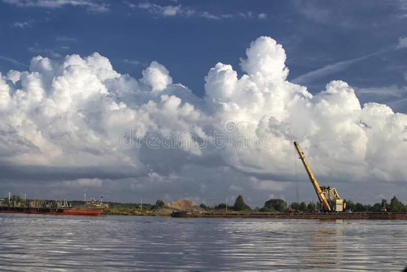 Versanden Sie die Aufladung auf Volga, Russland mit Kran und Boot lizenzfreie stockfotografie