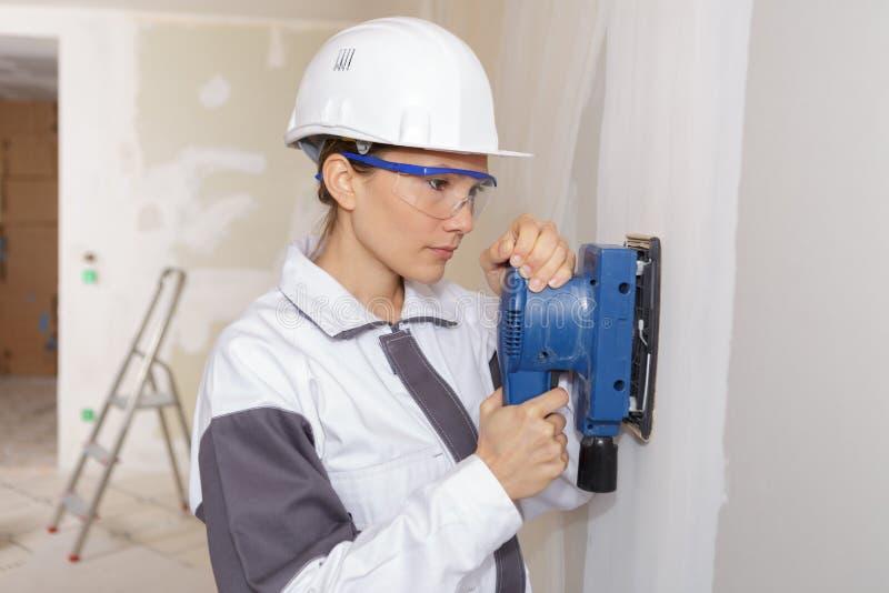 Versandende Wand des weiblichen Gipsers unter Verwendung der Energiesandpapierschleifmaschine lizenzfreie stockbilder