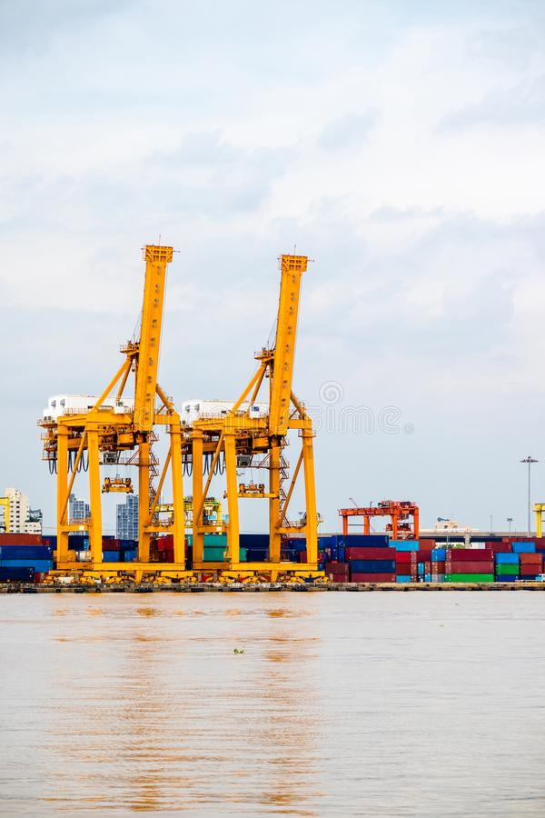 Versandhandelshafen BehälterFrachtschiffladen oder Entleerung durch Kranbrücke stockbild