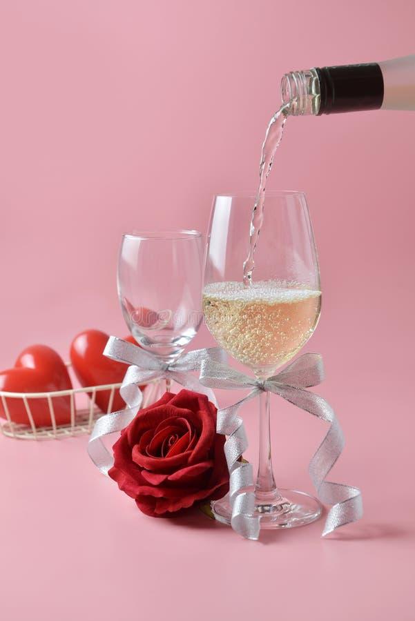 Versando dal vino bianco dalla bottiglia al vetro, con la rosa al fondo su fondo rosa Concetto del giorno del ` s del biglietto d fotografia stock libera da diritti