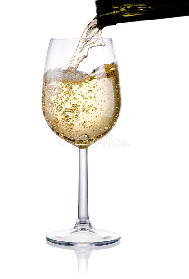 Versando un vetro di vino bianco isolato su bianco fotografia stock