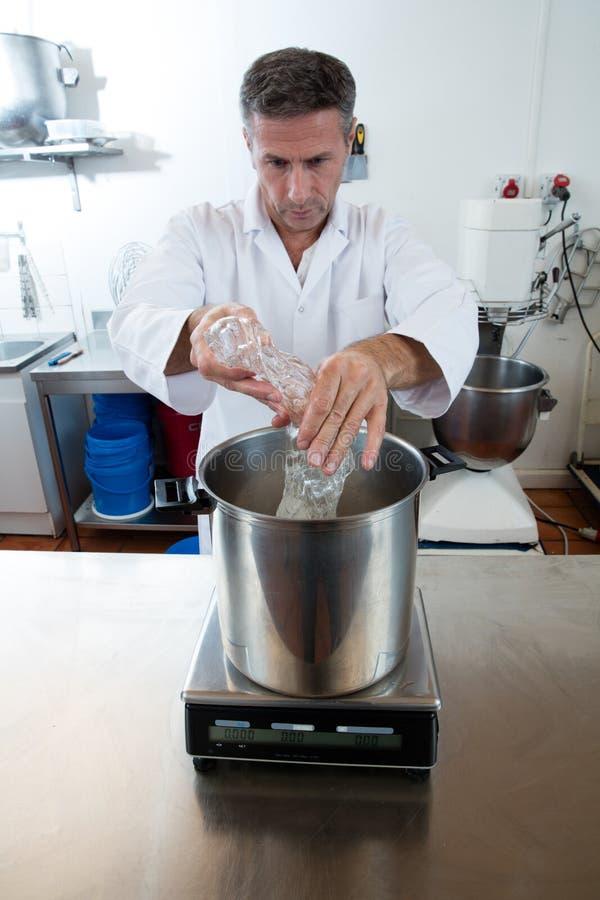 Versant et pesant le glucose sur l'échelle industrielle pour la spécialité douce photos stock