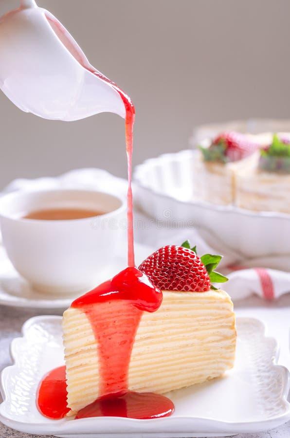 Versare la salsa di fragola su una deliziosa torta di crepe su una piastra bianca Il concetto di atmosfera emotiva della mattina immagine stock