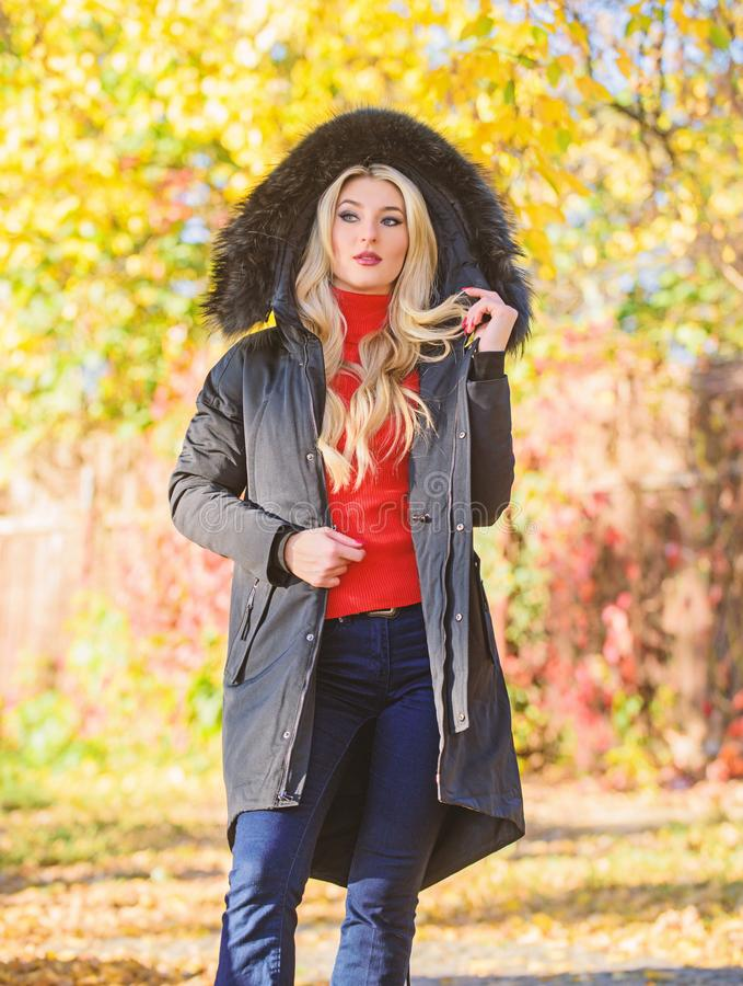 Versatile functional and stylish. Girl wear parka while walk park. Puffer jacket with hood. Woman wear black parka fur. Hood. Youth hipster fashion concept royalty free stock photo