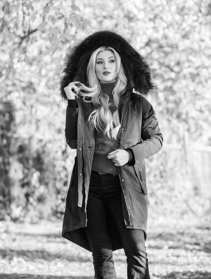 Versatile functional and stylish. Girl wear parka while walk park. Puffer jacket with hood. Woman wear black parka fur. Hood. Youth hipster fashion concept royalty free stock photography