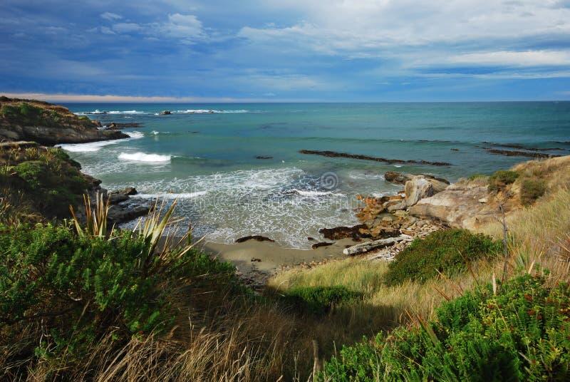 Verschönern Sie Bild eines ozeanischen Strandes mit schwermütigem Himmel landschaftlich lizenzfreies stockfoto