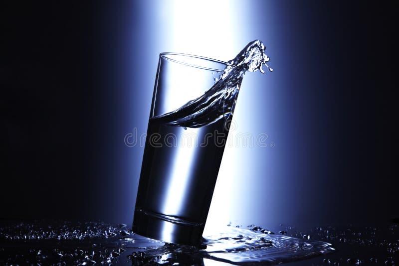 Verschütten des Glases Wassers stockfotos