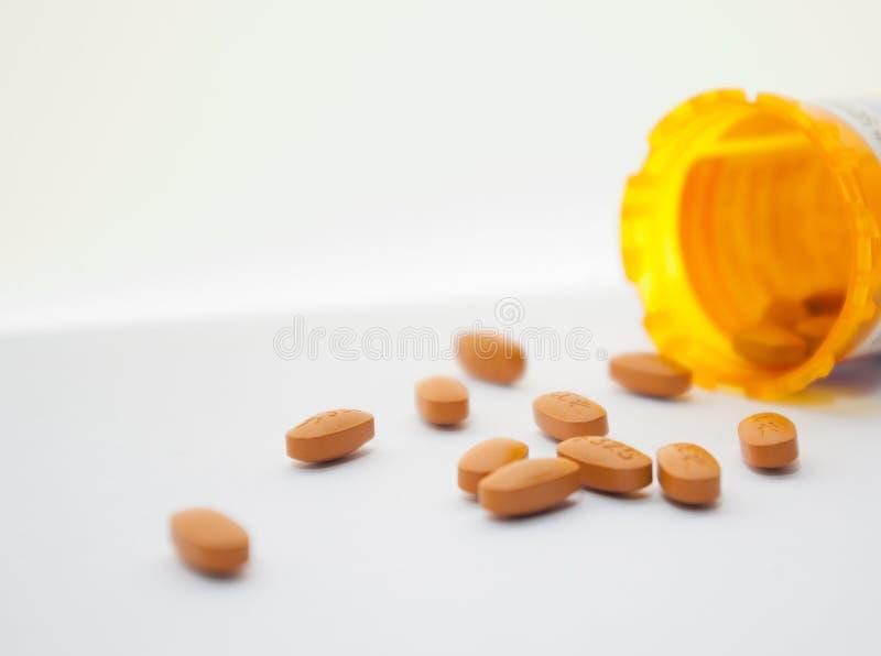 Verschüttete orange Pillen auf weißer Oberfläche stockfoto