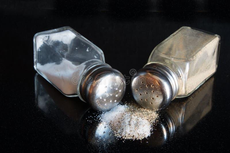 Verschüttete Salz- und Pfefferschüttele-apparat auf einem schwarzen Hintergrund stockbild
