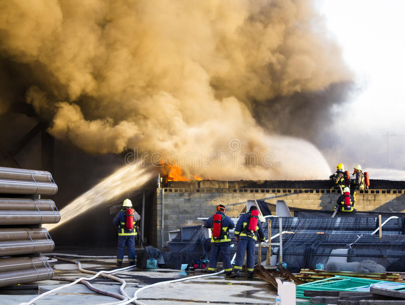 Verscheidene brandbestrijders steunen aan van de installatiebrand royalty-vrije stock afbeeldingen