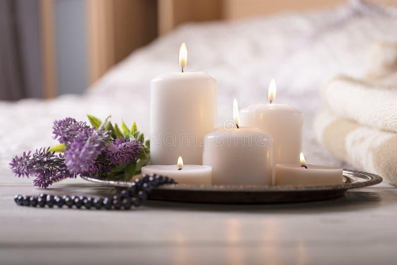 Verscheidene brandende kaarsen met bloem op bedlijst in licht comfortabel slaapkamerbinnenland Selectieve nadruk stock fotografie