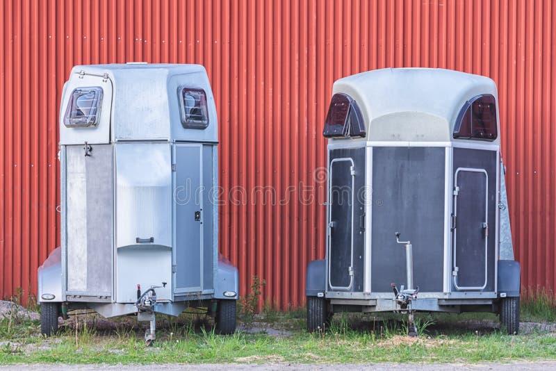 Verscheidene die aanhangwagens van het paardvervoer op het gras worden geparkeerd royalty-vrije stock afbeeldingen