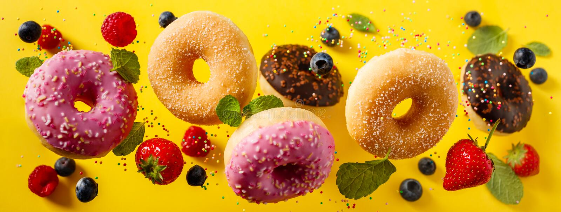 Verscheidene gedecoreerde donuts met sprinken en bessen in beweging die op gelloyale achtergrond vallen stock foto's