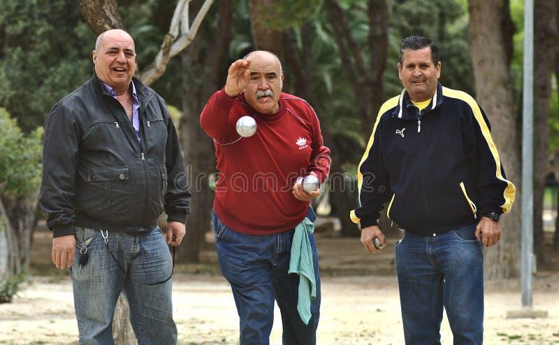 verscheidene gepensioneerden spelen het spel van petanque in het openbare park royalty-vrije stock afbeeldingen