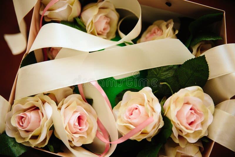 Verscheidene gevoelige rozen liggen in een doos met een boog stock foto's