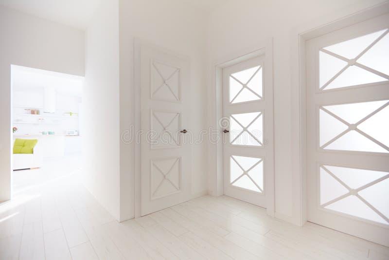 Verscheidene houten deuren met decoratieve glastussenvoegsels in gang van moderne flat stock afbeelding