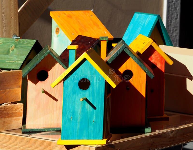 Verscheidene houten vogelhuizen in verschillende heldere kleuren stock afbeeldingen