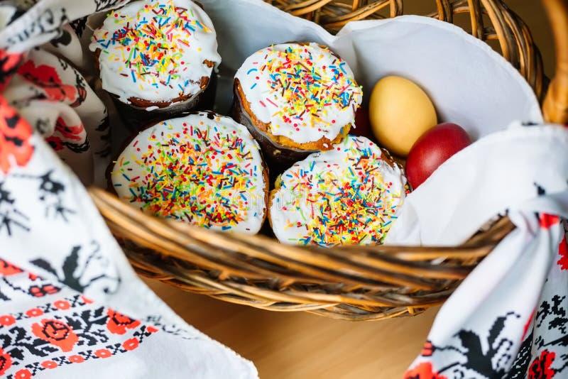 Verscheidene Kulich, een traditioneel Russisch Pasen-brood met schuimgebakje en kleurrijk bestrooit eieren op handdoek in de mand stock foto