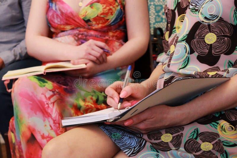 Verscheidene meisjes schrijven informatie over de trainingscursus in het notitieboekje neer stock afbeelding