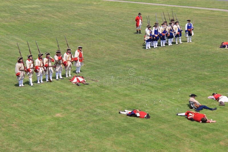 Verscheidene mensen kleedden zich in militair` s uniformen, gebruikend geweren tijdens de oorlogsweer invoeren, Fort Ontario, Osw royalty-vrije stock foto