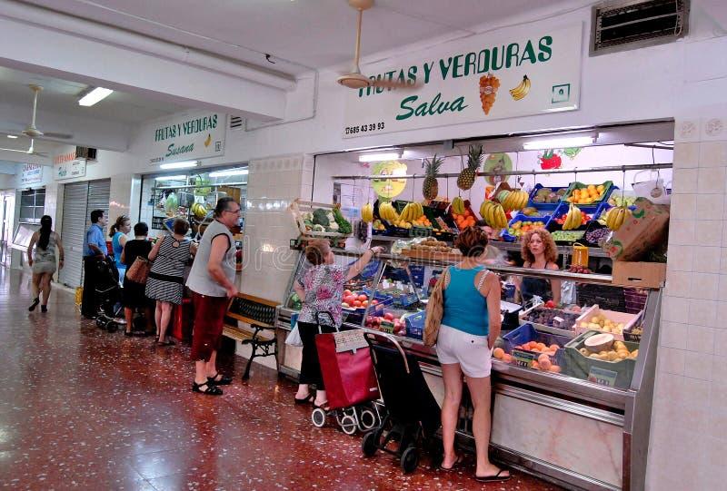 Verscheidene mensen kopen vruchten en groenten in de voedselgalerijen stock afbeeldingen