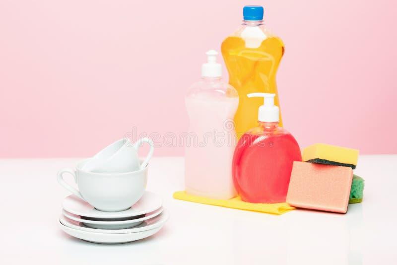 Verscheidene platen, een keuken sponst en plastic flessen met natuurlijke dishwashing vloeibare zeep in gebruik voor handdishwash royalty-vrije stock afbeelding