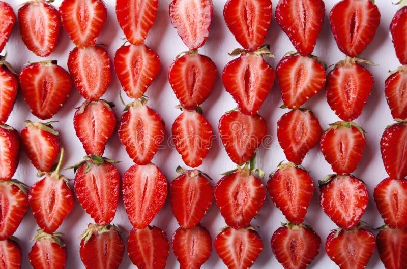 Verscheidene rijen van gesneden aardbeien op de witte achtergrond stock foto's