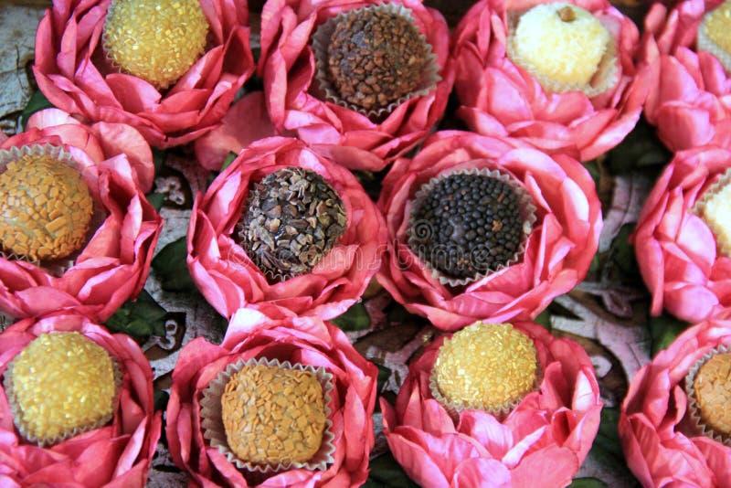 Verscheidene smakelijke die Bonbon in decoratieve, bloemenkoppen wordt geplaatst stock fotografie