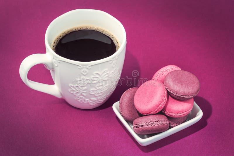 Verscheidene smakelijke roze makarons in kom en koffie stock afbeeldingen