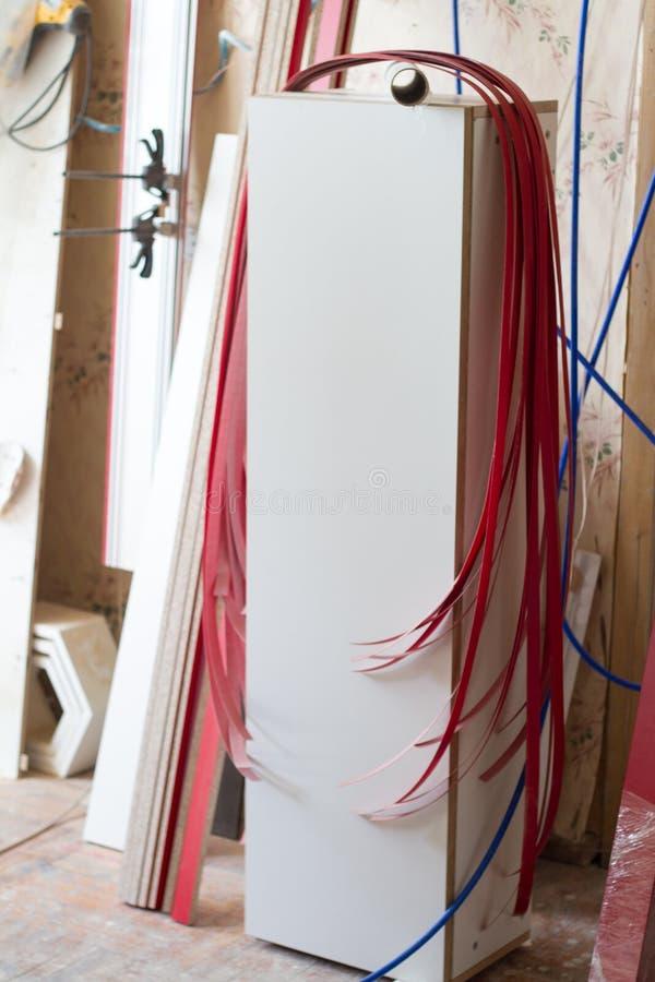 Verscheidene stukken van de rode rand en de melanine van pvc voor de vervaardiging van meubilair hangen op onvolledige kast op ee royalty-vrije stock foto