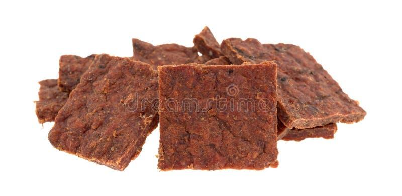 Verscheidene stukken van peppered rundvlees schokkerig op een witte achtergrond stock afbeeldingen