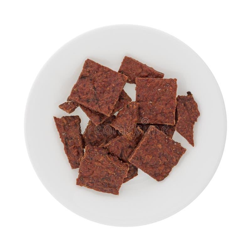 Verscheidene stukken van peppered rundvlees schokkerig op een witte plaat royalty-vrije stock foto's