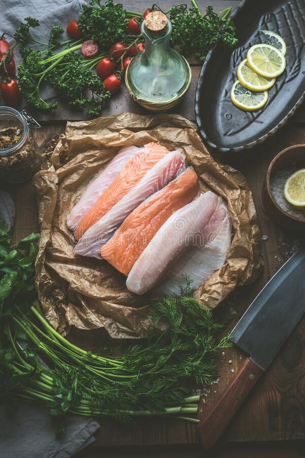 Verscheidene verse ruwe visfilets op keukenachtergrond met kruiden, specerijen en citroenmoten Selectie van kleurloze rauwe vis royalty-vrije stock fotografie