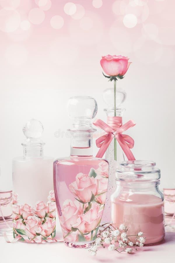 Verscheidenheid van cosmetische productflessen met rozenessentie die zich op witte roze achtergrond met bokeh bevinden Huidzorg,  stock afbeelding
