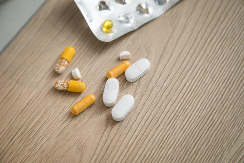 Verscheidenheid van de gele en witte geneeskunde en de blaar van pillentabletten op houten achtergrond met exemplaarruimte royalty-vrije stock foto