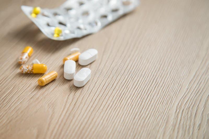 Verscheidenheid van de gele en witte geneeskunde en de blaar van pillentabletten op houten achtergrond met exemplaarruimte stock afbeeldingen
