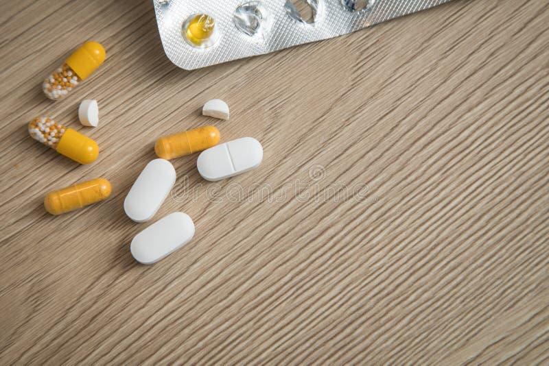 Verscheidenheid van de gele en witte geneeskunde en de blaar van pillentabletten op houten achtergrond met exemplaarruimte stock foto's
