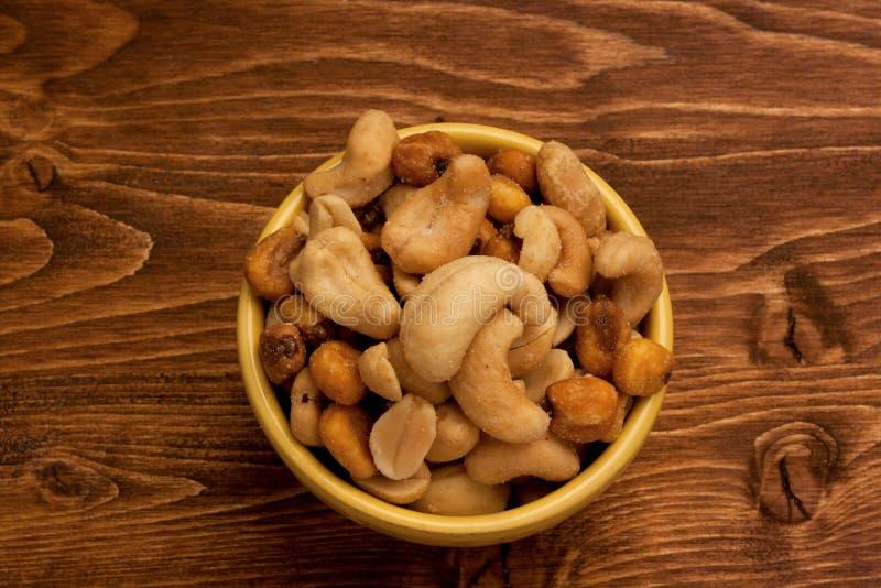 Verscheidenheid van gezouten snacks op houten achtergrond stock afbeelding