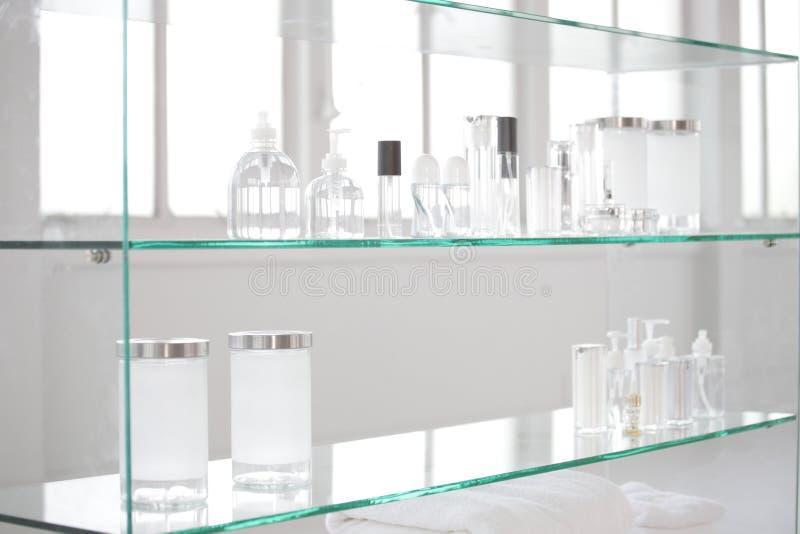 Verscheidenheid van glasflessen op glasplank stock foto