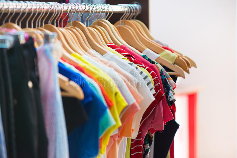 Verscheidenheid van kleren die op rek hangen royalty-vrije stock afbeeldingen