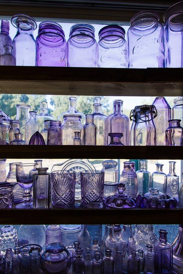 Verscheidenheid van kristalglazen en kruiken op planken royalty-vrije stock afbeeldingen