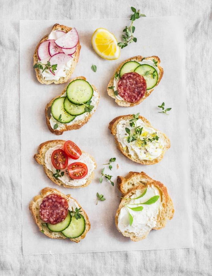 Verscheidenheid van minisandwiches met roomkaas, groenten en salami Sandwiches met kaas, komkommer, radijs, tomaten, salami, t royalty-vrije stock fotografie
