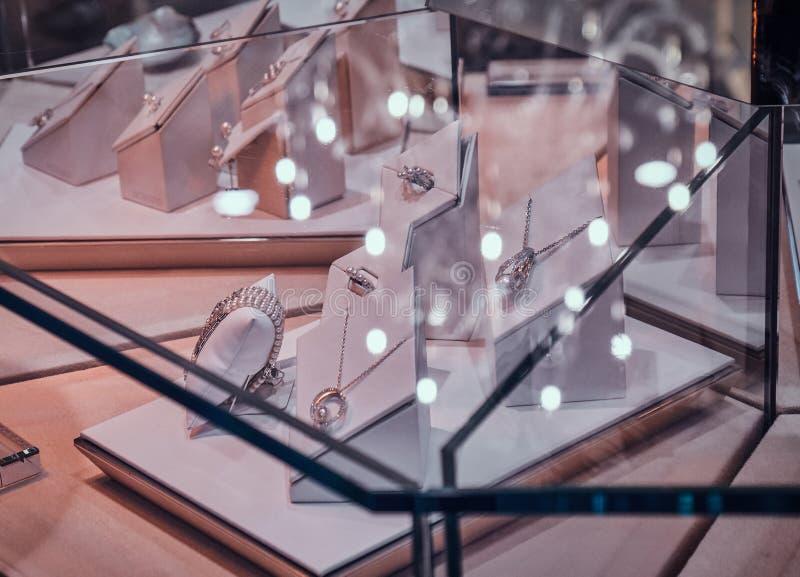 Verscheidenheid van mooie gouden versieringen op de witte vertoning onder het glas in juwelenwinkel royalty-vrije stock foto's