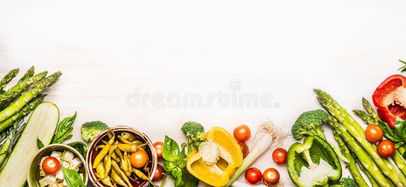 Verscheidenheid van organische groenteningrediënten met asperge en feta voor het heerlijke seizoengebonden koken, witte houten ac royalty-vrije stock afbeelding