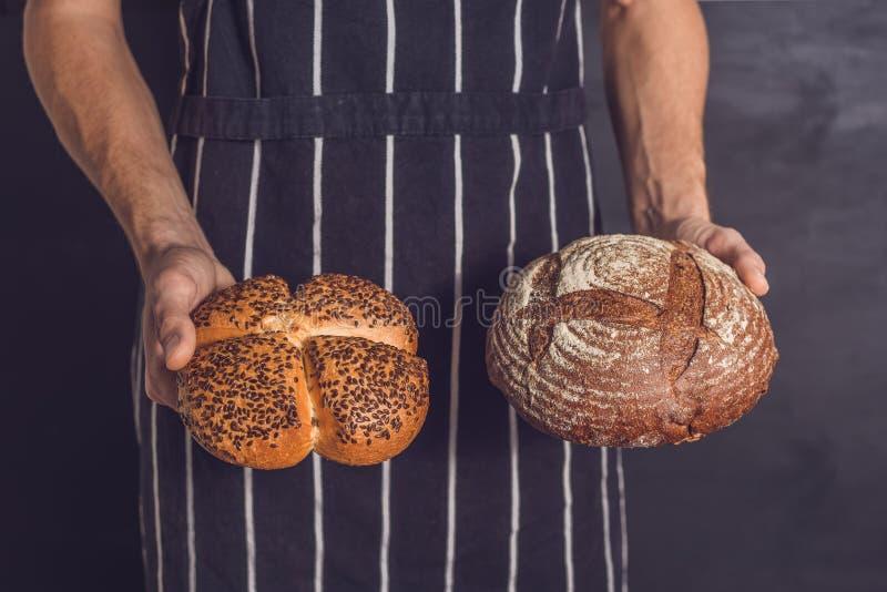 Verscheidenheid van vers gebakken broden in jonge bakkershanden hipster stock afbeelding