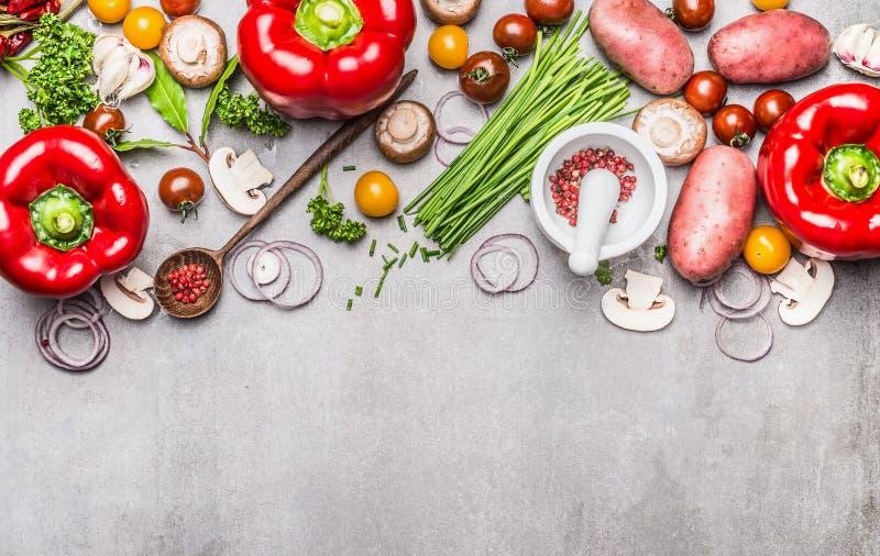 Verscheidenheid van vers organisch groenten en kruiden voor het smakelijke vegetarische koken met mortier, stamper en houten lepe stock foto
