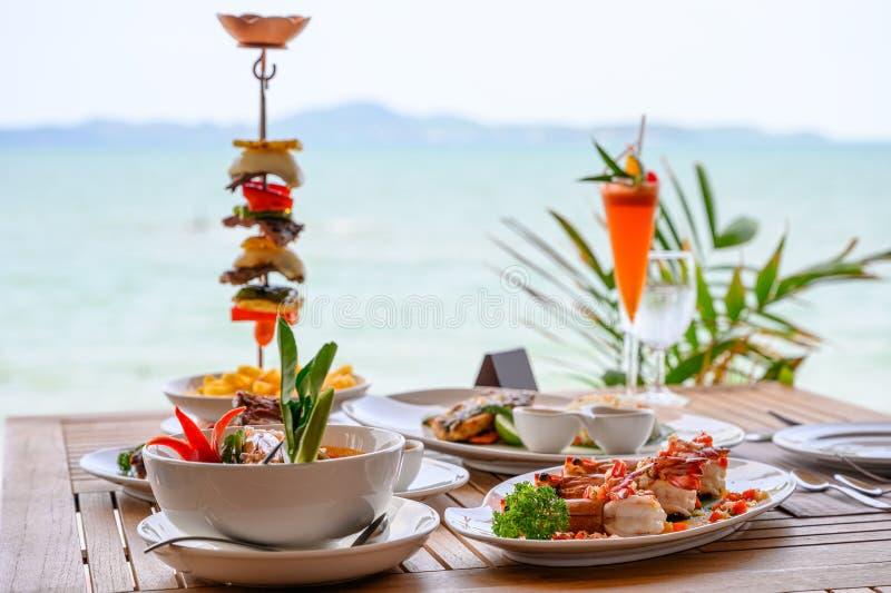 Verscheidenheid van voedsel, geroosterde varkensvleesribben, rundvleeslapje vlees, zeevruchten en kruidige soep op eettafel stock afbeeldingen