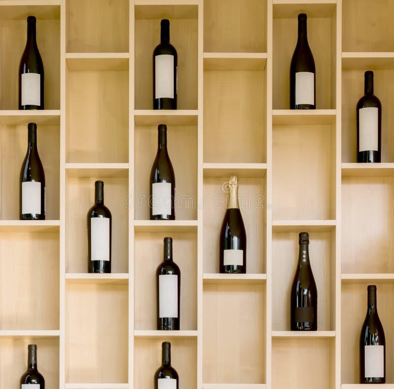 Verscheidenheidsflessen wijn en champagne in een houten vitrine in de opslag stock afbeelding