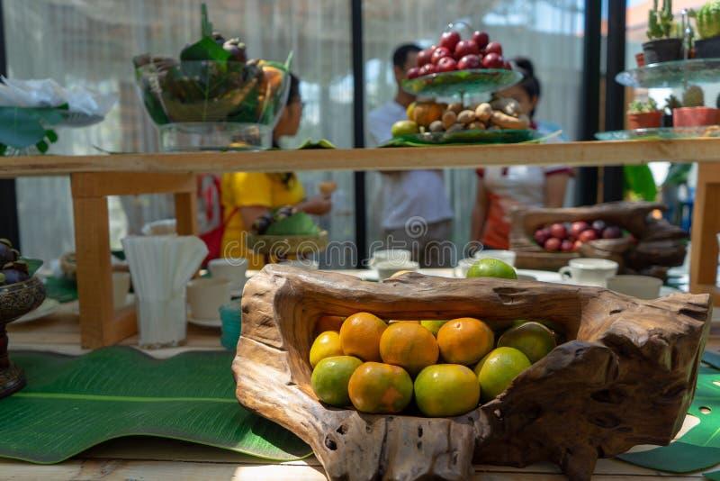 Verscheidenheidsvruchten zoals rambutan oranje mangostan rode pruim op de houten tegenbar voor seminarie pepole in openlucht bij  royalty-vrije stock afbeelding
